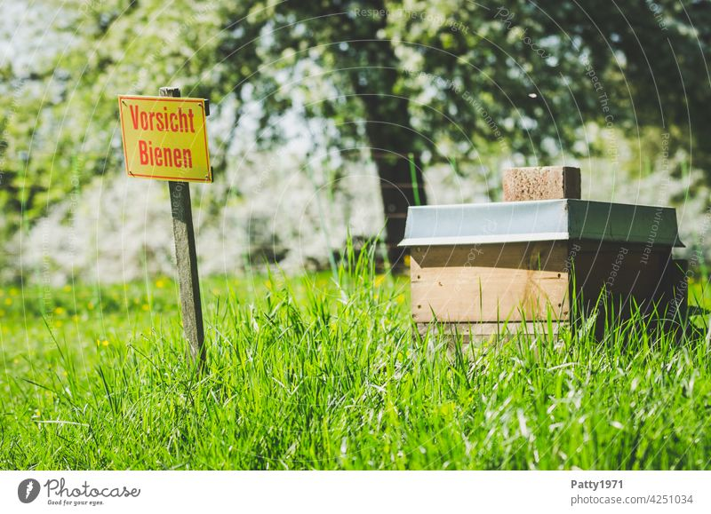 """Recommendation   A warning sign in front of a beehive on a green meadow reads """"Caution bees"""". Beehive Warning sign beekeeping Insect Nature Meadow Bee-keeping"""