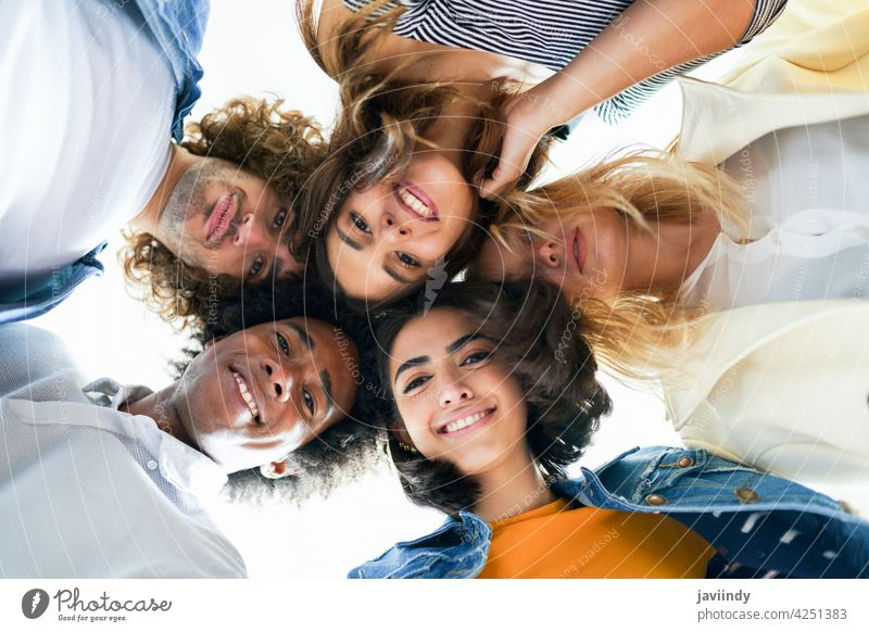 Multi-ethnic group of friends with their heads together in a circle. people young multi-ethnic multiracial diversity lifestyle outdoors portrait women laughing