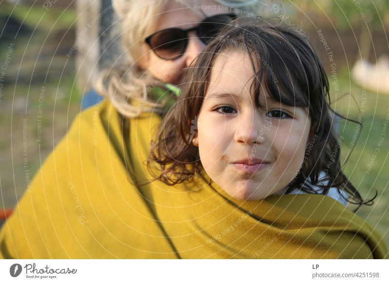 girl in her mothers arms protected by a scarf Downward Looking Profile Upper body Portrait photograph Copy Space middle Copy Space bottom Copy Space top
