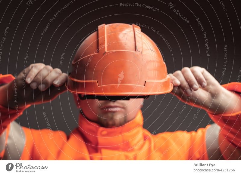Railway worker puts on safety helmet Service Face Workplace people rail Engineer youthful Hat Working man job masculine Engineering Protective Helmet Profession