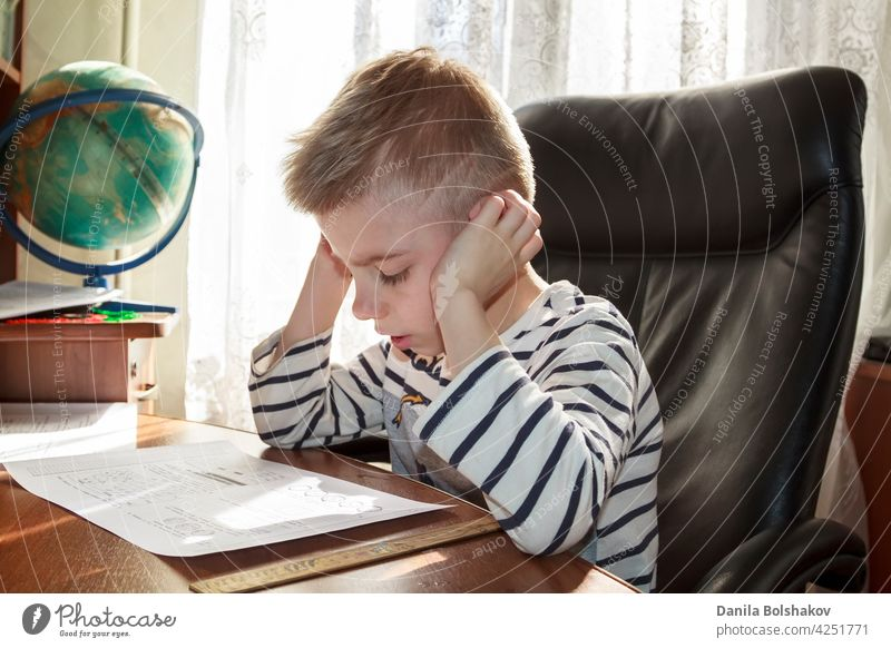 happy boy thinks over the lessons homework doing kid child little alone people person caucasian childhood education study learn school book writing cute