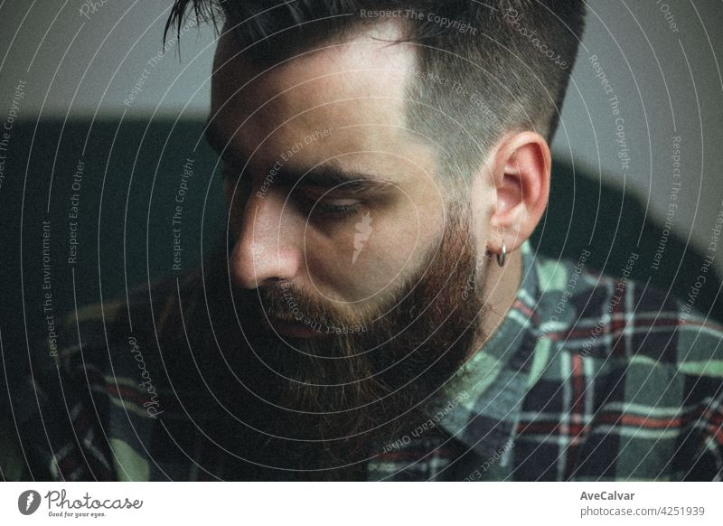 Young hipster man with a beard and a plaid shirt with shadows and copy space, portrait mental health concept lifestyles relaxation male people sitting young