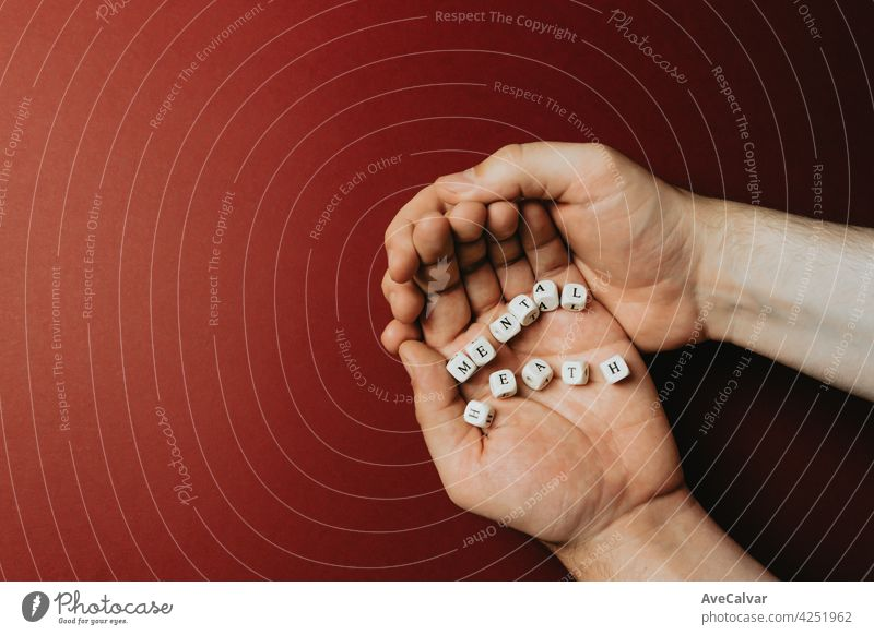 Hands holding one the words mental health over a dark red background, mental health concept with copy space Advice Help Patient Problem Psychological