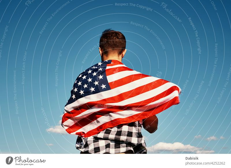 Man holds usa national flag against blue sky american outdoor man 4th july person waving people summer day stars stripes background beautiful independence