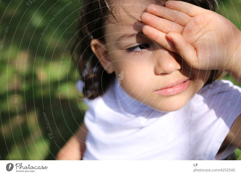 curious girl looking into the sun protecting her eyes with her hand watching surprise playful person learning kid face eyesight education discovery curiosity
