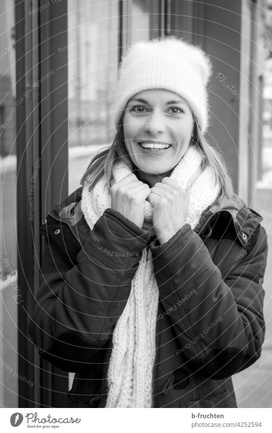smiling woman with wool cap, scarf and coat Scarf Woman Winter Cold Adults Cap Exterior shot portrait Woolen hat Coat Jacket hands stop Laughter Looking
