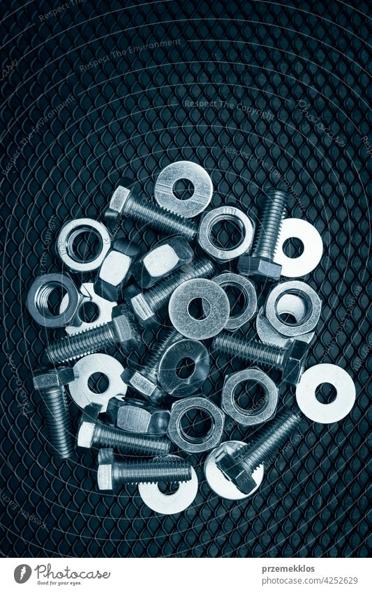 Bolts and nuts on steel surface. Mechanic items for maintenance. Hardware parts to build and repair. Technical tools background metal hardware iron heavy use