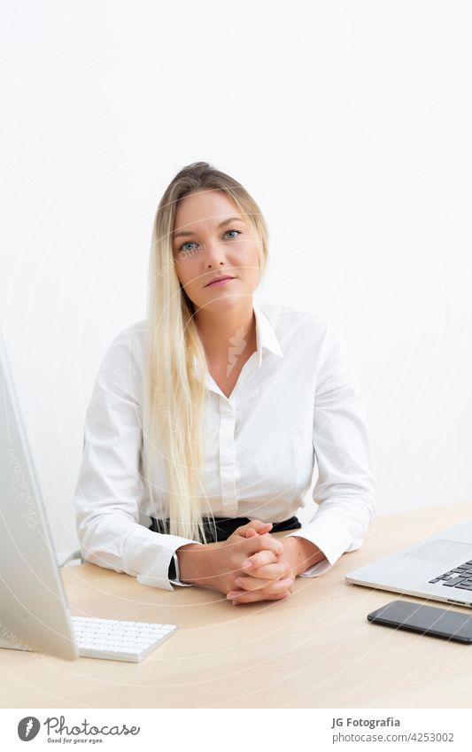 Young attractive businesswoman looking at camera in office. working corporate occupation girl career fashionable portrait pretty employee worker modern trendy