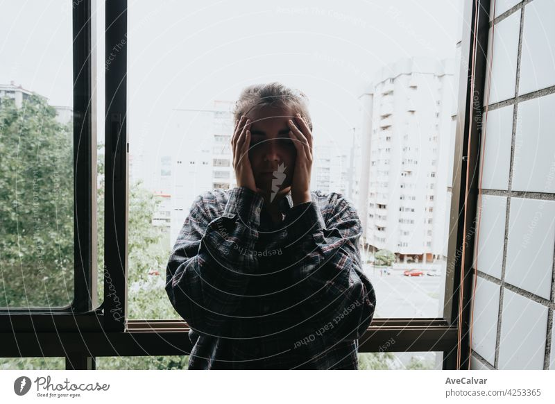 Worried woman looking from the window of her flat, mental health concept in the city, depression with copy space anxiety frustration problem sad sadness