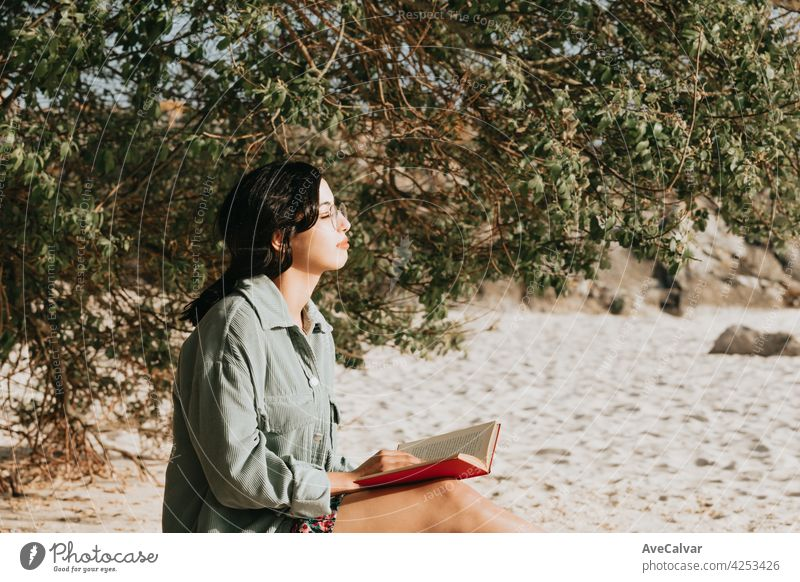 Young Moroccan woman on modern clothes sitting on the beach reading a book during a sunny day with copy space inspirational and relax theme with colorful tones