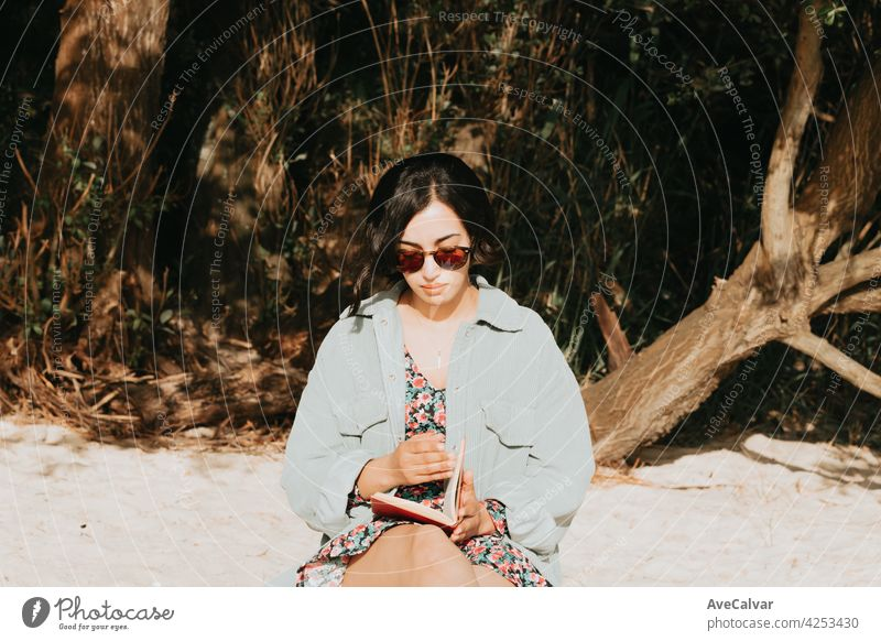 Young Moroccan woman on modern clothes using sunglasses sitting on the beach reading a book during a sunny day with copy space inspirational and relax theme with colorful tones