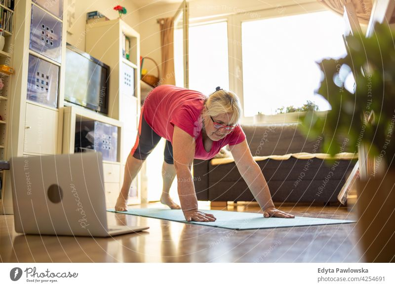 Senior woman exercising at home eyeglasses wrinkles natural real people casual day lifestyle grandmother pensioner aged leisure retirement retired one person