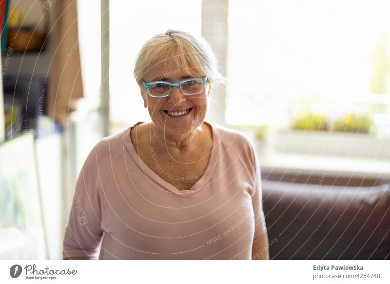 Happy senior woman smiling at home eyeglasses wrinkles natural real people casual day lifestyle grandmother pensioner aged leisure retirement retired one person
