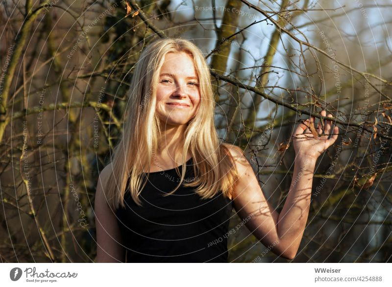 A laughing blonde girl plays with the branches of a tree and is happy about the sun in the forest Girl pretty Attractive cheerful Cheerful Smiling Laughter Tree