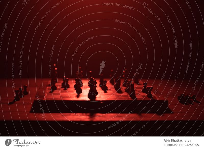 Chess board with chess pieces table still life dark shadow red light color objects halo Chessboard Playing Horse King pawn bishop Intellect Queen Colour photo