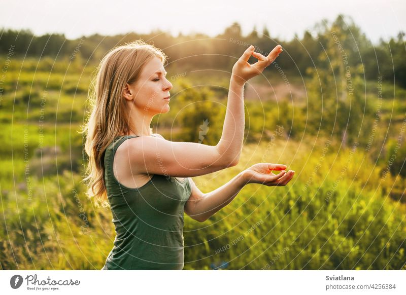 Beautiful blonde does yoga in the fresh air. The concept of mental health and healthy lifestyle young woman asana outdoors nature relax girl female summer