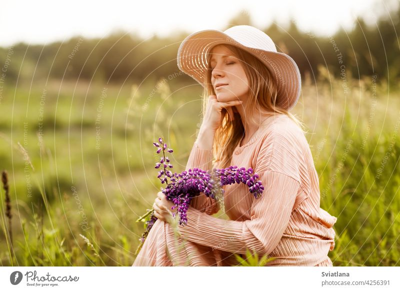 Portrait of a beautiful blonde with a bouquet of lupines in her hands sitting on the lawn girl field hat summer young dress flower beauty portrait