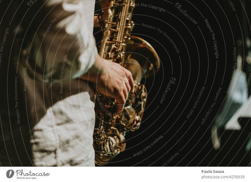close up hand holding saxophone Saxophone Saxophon player Music Musician Musical instrument Art Sound Human being Man Classical Jazz Concert Brass Elegant Style