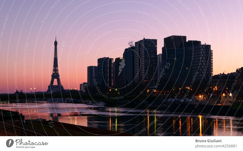 Paris, France. March 07. 2021. The city at sunrise or sunset. View on the quayside of the Seine river. Eiffel Tower in the background. Modern buildings of Beaugrenelle district. Editorial usage only.