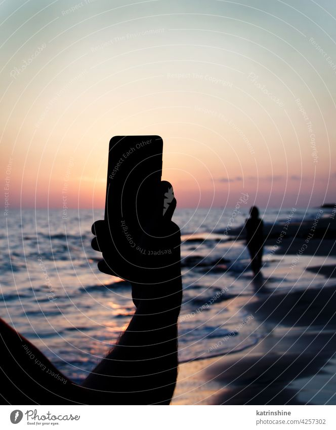 Man takes a sunset photo of girlfriend on the mobile phone sky sea men taking picture women silhouette faceless hand cellphone cellular nature outdoor cityscape