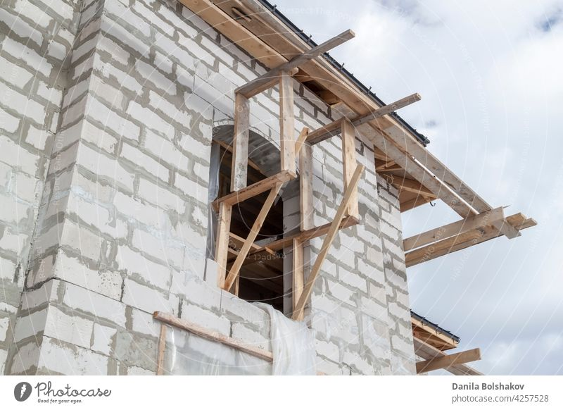 close up view of scaffolding and house under construction with holders for gutters water drainage system of roof installation soffit repair guttering wooden