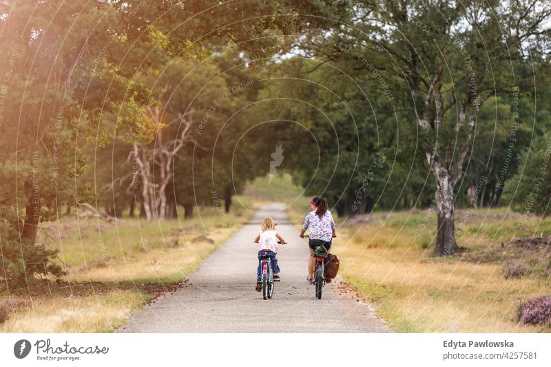 Mother and daughter cycling together in the forest family safety people girls children kids biking bike cycle Culture Dutch Europe Holland Netherlands Outdoor