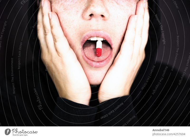 A woman is holding a pill, capsule with a drug on her tongue, teenager taking xtc.cocaine or other drugs or medicine background medical fashion design love