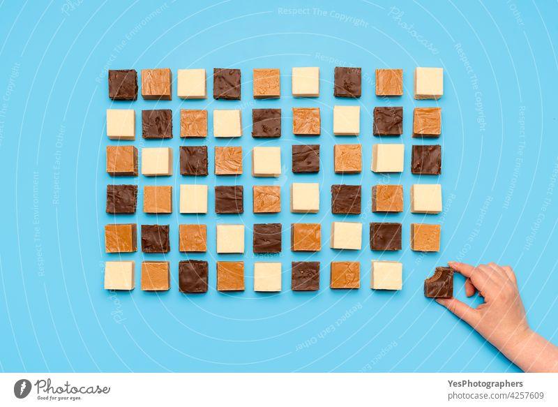Fudge assortment aligned symmetric on blue table. Woman grabbing chocolate fudge, top view above abundance american background bite brown candy caramel
