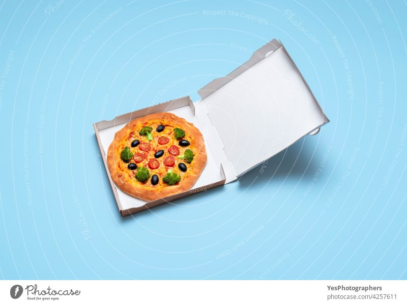 Vegan pizza in a cardboard box. Healthy vegan pizza delivery above background baked blank blue broccoli carton cheese color copy space crust cuisine cut out
