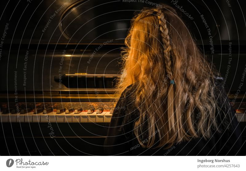 Girl playing piano, rear view, sidelight Piano Piano keyboard Light and shadow mood hair Rear view hairstyle Child concentration braid one person