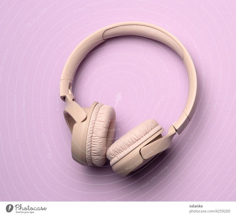 beige wireless headphones on a purple background equipment music personal stereo audio sound modern studio device technology headset digital listen