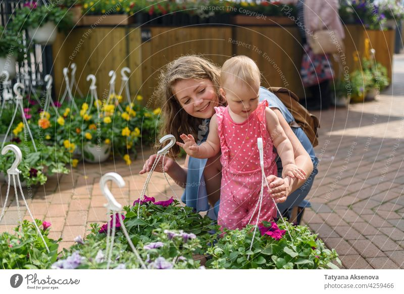 Woman with daughter choosing flowers on market woman shopping garden plant buying retail gardening gardener female young green caucasian store smiling adult