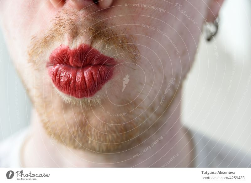 Bearded man with red lipstick beard make-up face gay homosexual lgbtqia male trans person portrait adult mouth transgender caucasian headshot individuality
