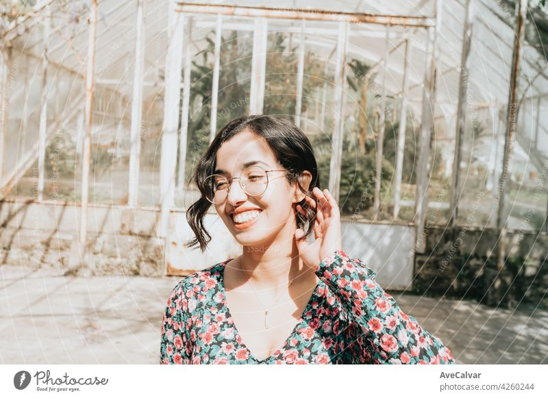 Young Moroccan woman smiling to camera in autumnal and desaturated colors with copy space and modern clothes curly hipster teenager female moroccan young