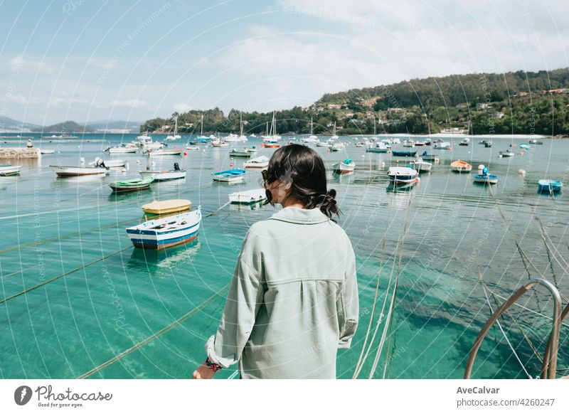Woman backwards in front of the sea with a lot of boats during a sunny day person female portrait woman alone glamour joy sunlight yacht young brunette