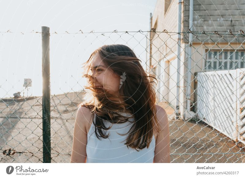 Young woman with long hair moving his hair during a sunset with liberty and freedom concept and mental health with copy space model smile wind face happy urban