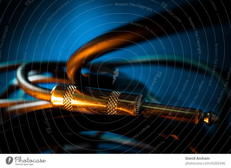 Macro Closeup of Metal Quarter Inch Instrument Cable Connector Laying Horizontally on Cord in Front of Teal Background with Orange Lighting quarter inch jack