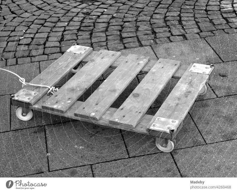 Lined wooden pallet with wheels for transporting boxes at the weekly market at the Bockenheimer Warte in Frankfurt am Main in Hesse, photographed in neo-realistic black and white