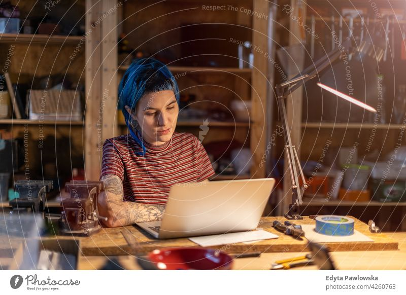 Young woman using laptop in her workshop diy hipster hair tattoos female owner profession service small business employee working workplace maintenance adult