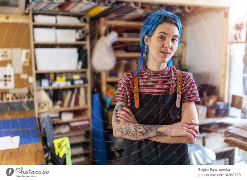 Confident young craftswoman in her workshop diy hipster colorful hair tattoos female owner profession service small business employee working technician