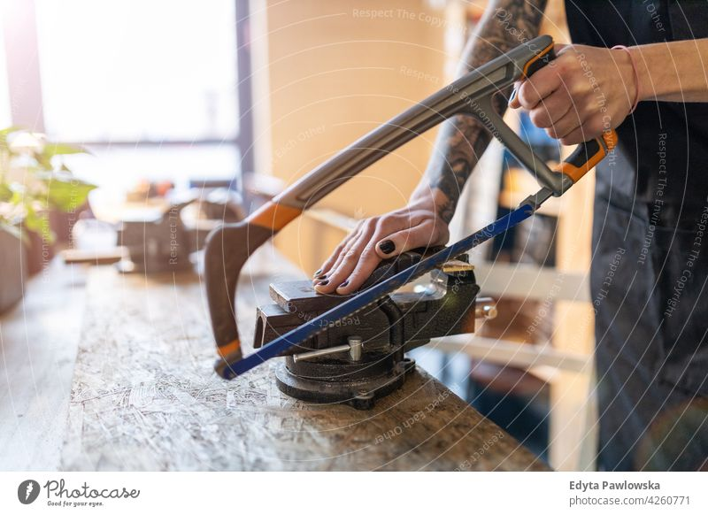 Woman using hand saw in her workshop diy hipster colorful hair tattoos woman female owner profession service small business employee working technician