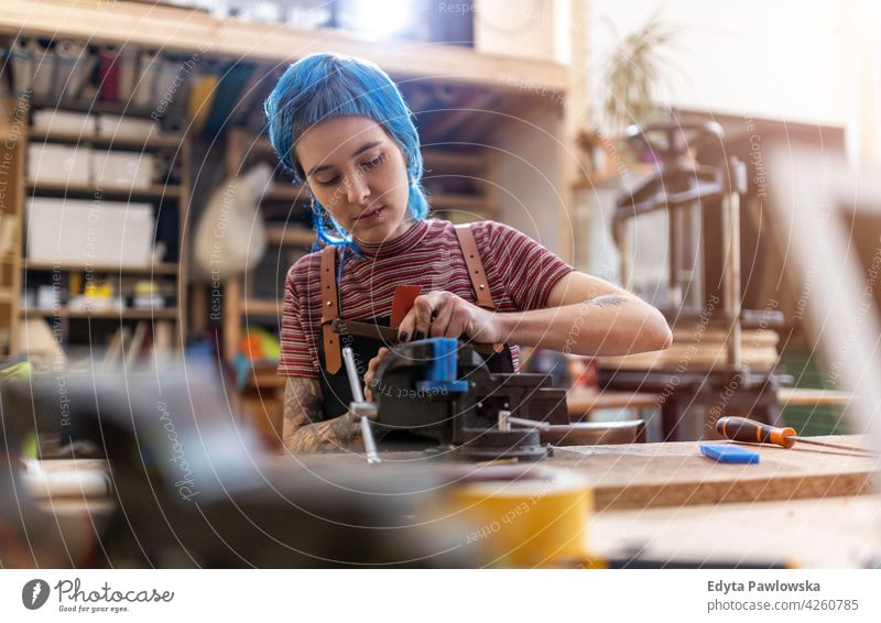 Craftswoman working in her workshop diy hipster hair tattoos female owner profession service small business employee workplace maintenance adult people expert