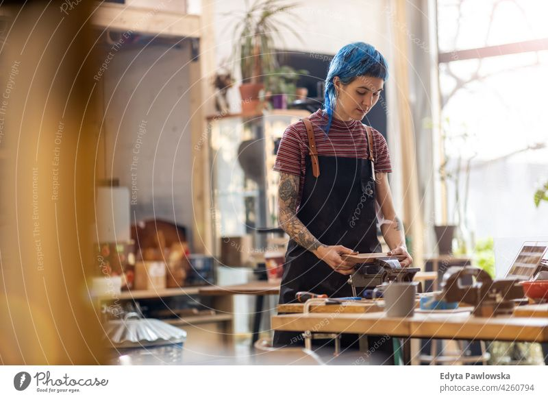 Female Carpenter In Her Workshop diy hipster hair tattoos woman female owner profession service workshop small business employee working workplace maintenance