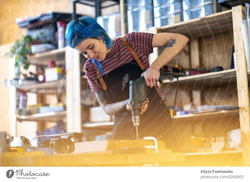 Young woman using electric drill in industrial workshop diy hipster colorful hair tattoos female owner profession service small business employee working