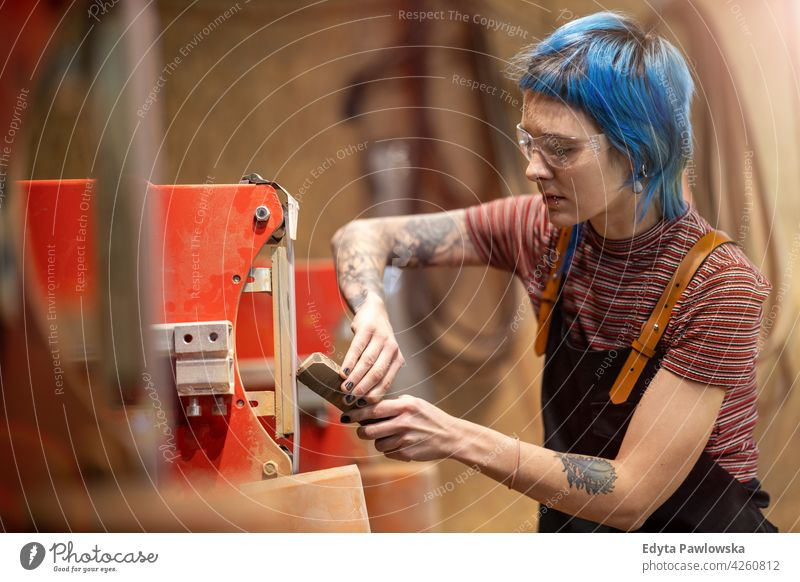 Young craftswoman during her work diy hipster hair tattoos female owner profession service workshop small business employee working workplace maintenance adult