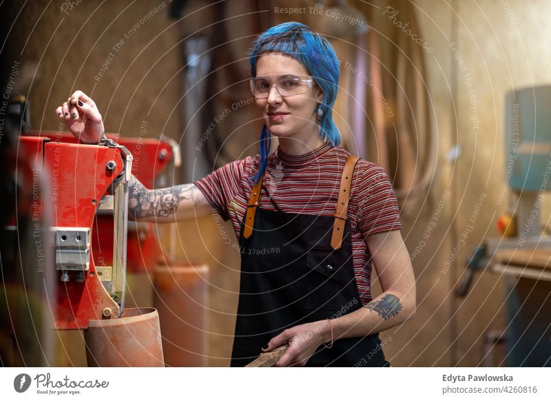 Female Carpenter In Her Workshop diy hipster colorful hair tattoos woman female owner profession service workshop small business employee working technician