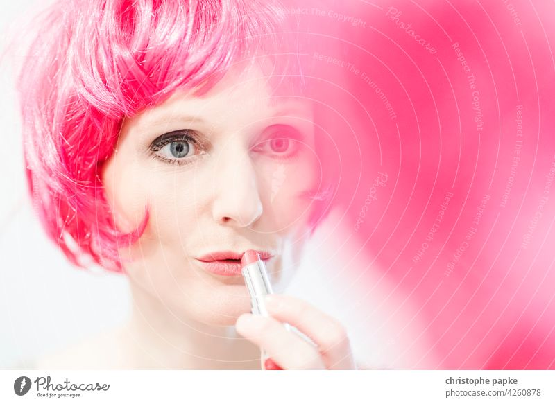 Woman in pink wig applies lipstick Wig Apply make-up Lipstick Hair and hairstyles Make-up Feminine Face Mirror Mirror image Cosmetics Young woman pretty Mouth