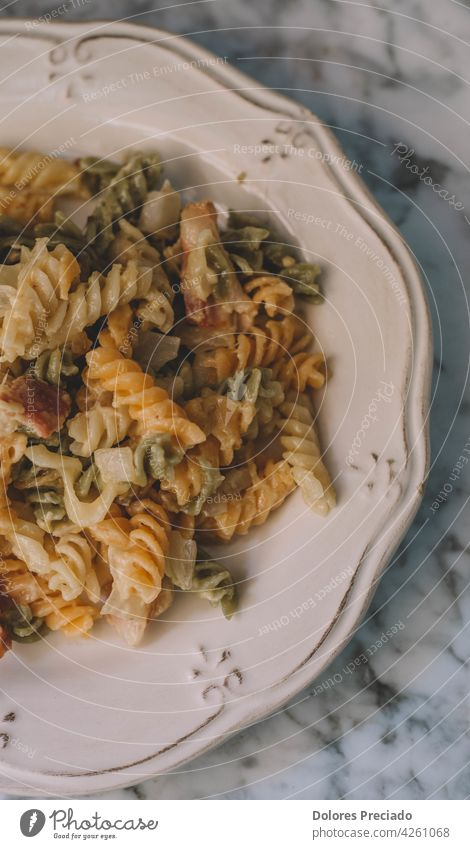 A plate of pasta with cream and bacon noodle penne fettuccine parmesan cream sauce spaghetti recipe homemade noodles pepper wooden mediterranean stone spicy