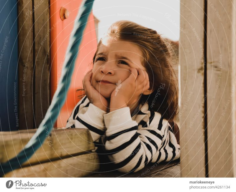 Portrait of a Caucasian little girl with her hands on her face in a pensive attitude innocence think tranquility loneliness real people thoughtful one person