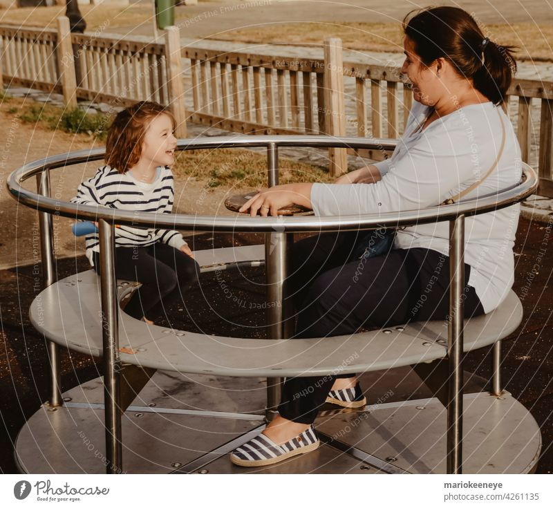 Mother and daughter having fun with a spinning wheel at a children's playground mother complicity females two people playing colours outdoors girls move